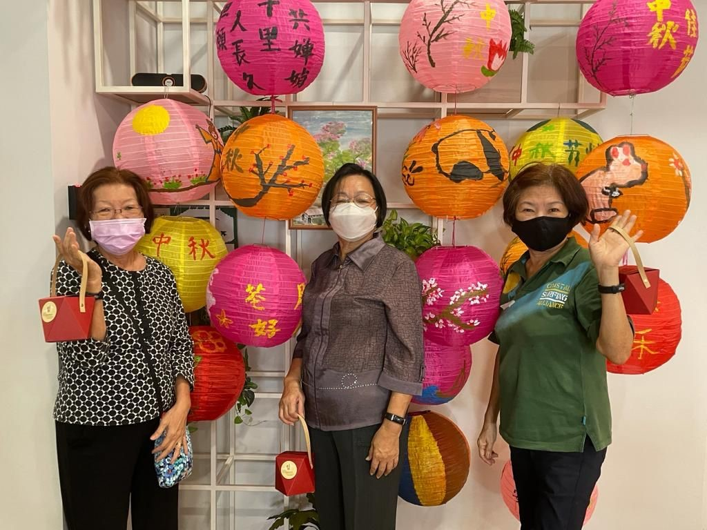 Yong-en Care Centre seniors posing gamely with their sponsored mooncakes and beautifully decorated lanterns
