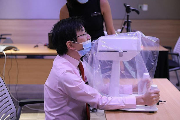 Dr Luke Tay, a consultant at SGH who was part of the team that developed the robot, demonstrating how a patient would position himself when undergoing a swab test done by the SwabBot.ST PHOTO ONG WEE JIN